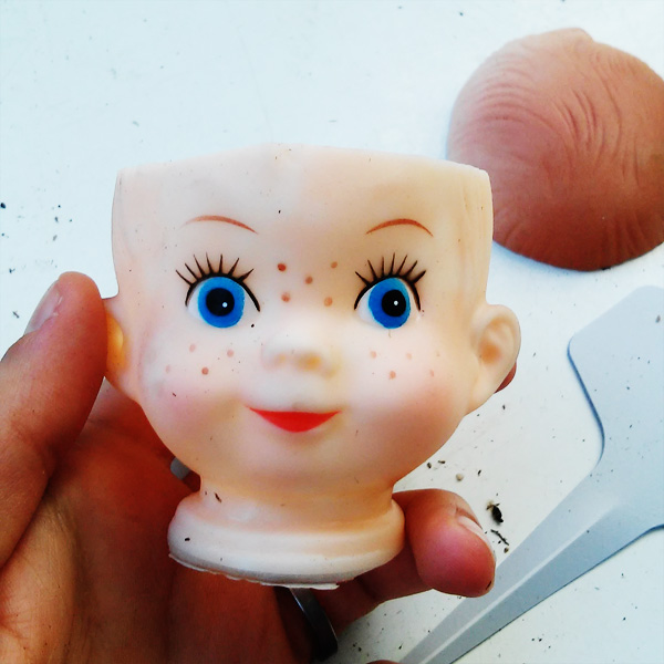 Making a mini planter out of a plastic baby doll head.